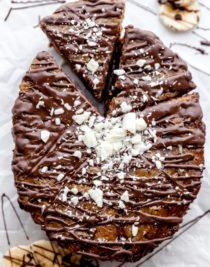 Chocolate chip banana bread on a piece of white parchment paper topped with melted dark chocolate and white chocolate shavings, with a piece cut out in a pie shaped, by the food cafe.