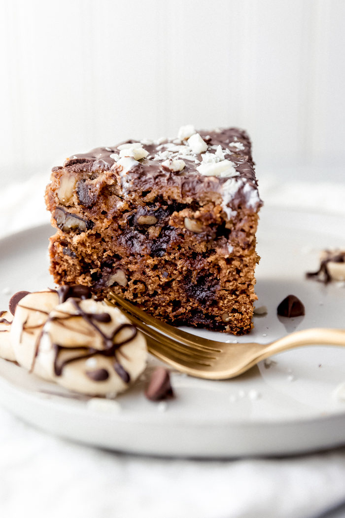 A slice or chocolate chip banana bread topped with melted chocolate and white chocolate shavings on a white plate with sliced bananas and chocolate chips on the plate served with a gold fork on a white background, by The Food Cafe.