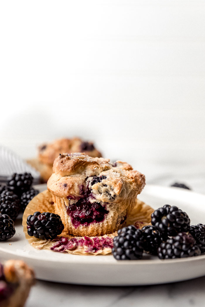 A blackberry muffin on a white plate surrounded by fresh blackberries on a white background showing the blackberries baked inside the muffin, by The Food Cafe.
