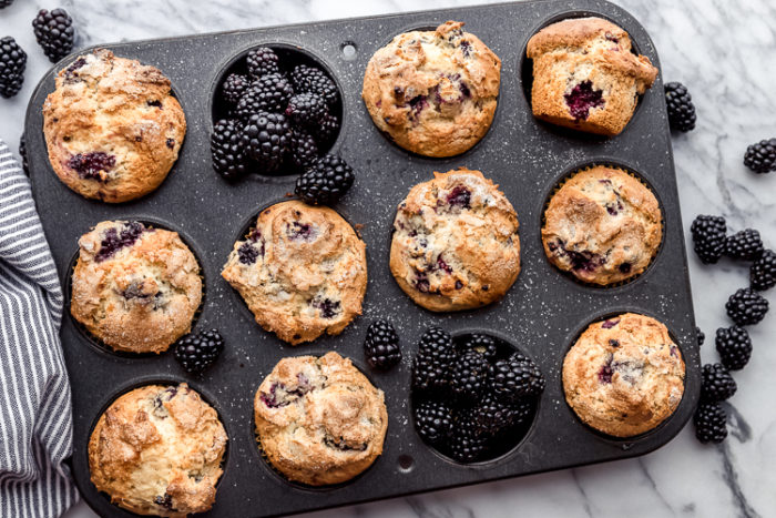 Blackberry muffins in a dark muffin pan with two muffin cups filled with blackberries on a white background, perfect breakfast side by The Food Cafe.