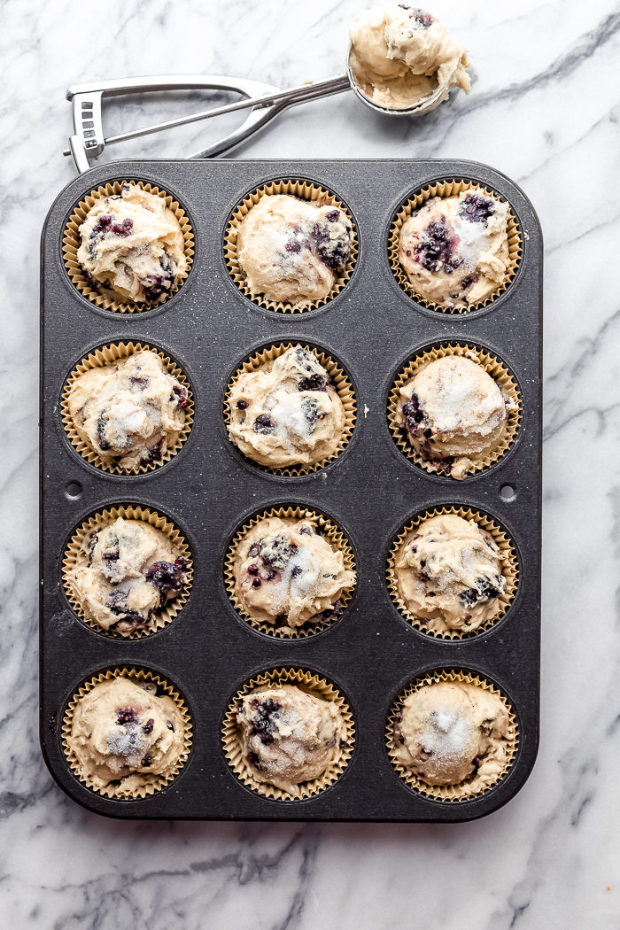 A 12 cup black muffin pan filled with tan muffin liners and blackberry muffin batter on a light background, by The Food Cafe.