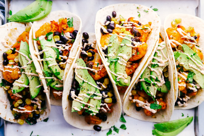 cauliflower tacos lined up on a silver serving tray lined with white parchment paper and topped with sliced avocado and Mexican crema, by The Food Cafe