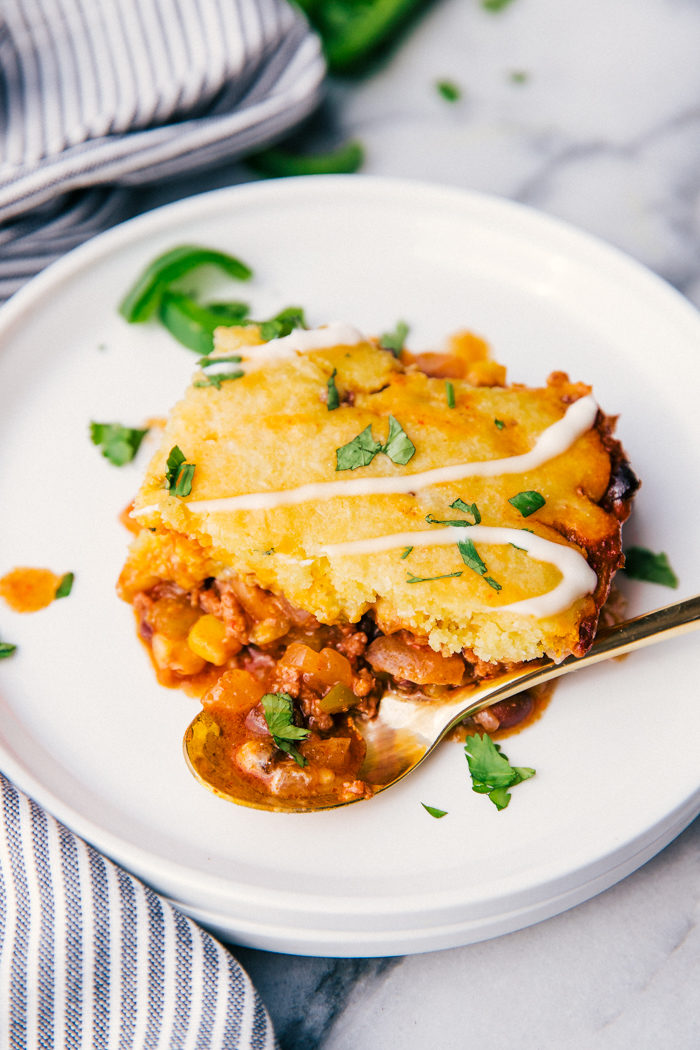 A slice of Mexican cornbread casserole on a white place with a gold spoon drizzled with sour cream and topped with chopped cilantro, by The Food Cafe.
