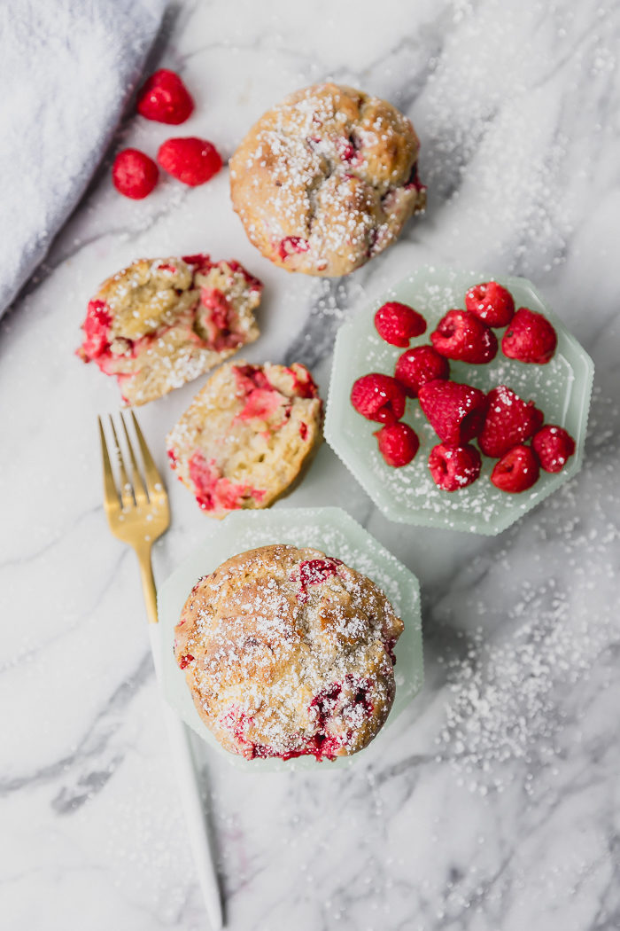 Three raspberry muffins on a white background, two dusted with powdered sugar and the one in the middle is sliced to see the raspberries inside by The Food Cafe.
