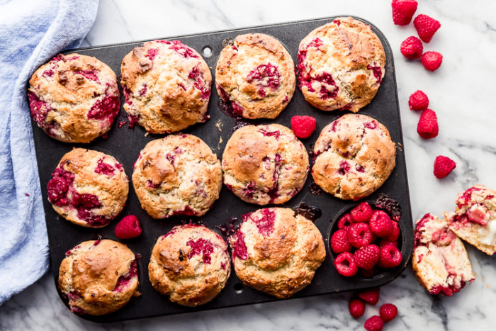 A 12 cup black muffin tin filled with fresh homemade raspberry muffins on a white background with fresh raspberries off to the side, by The Food Cafe