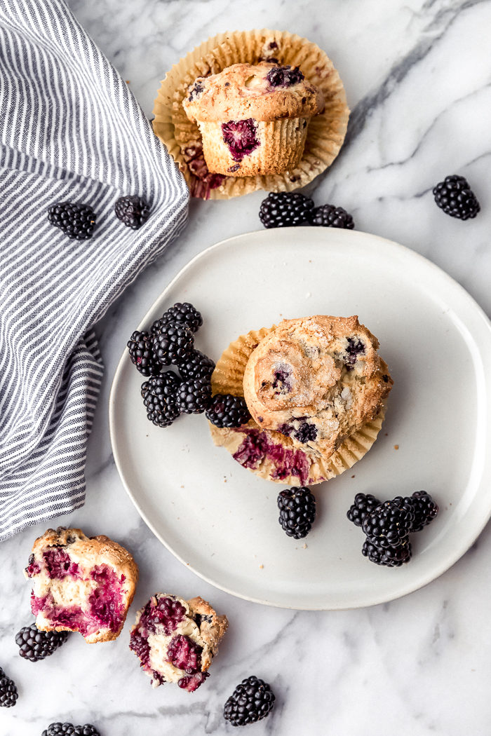 Three Blackberry muffins on a white background on muffin sitting on a white plate, one muffin cut in half to show all the blackberries inside, and one muffin laid on its side with a tan muffin liner underneath it with fresh blackberries scattered around each muffin, by The Food Cafe.