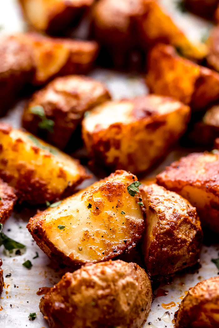 oven roasted red potatoes on a sheet pan seasoned with taco seasoning and fresh chopped parsley, the perfect summer side dish by The Food Cafe.