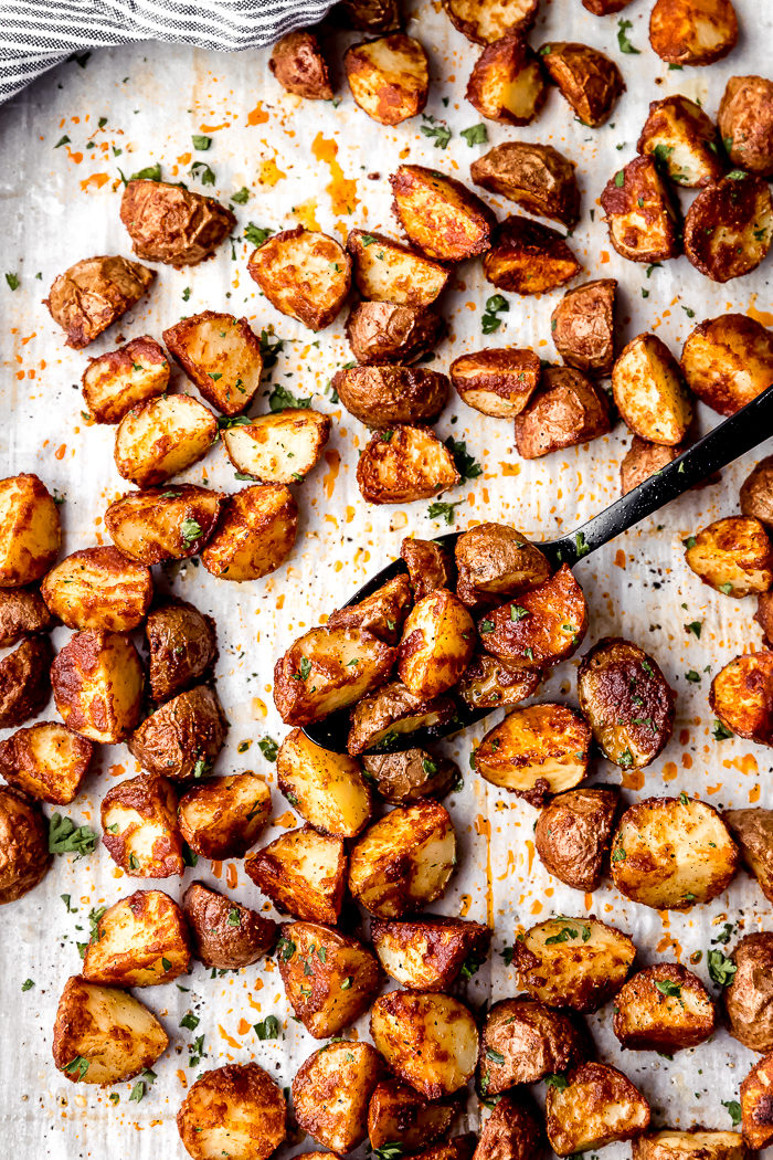 Oven roasted red potatoes on a baking sheet lined with white parchment paper with a black serving spoon to spoon potatoes up, by The Food Cafe.