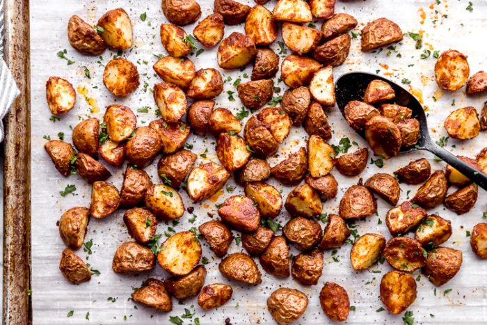 Oven roasted red potatoes on a sheet pan lined with white parchment paper, using a black serving spoon to remove from pan, by The Food Cafe