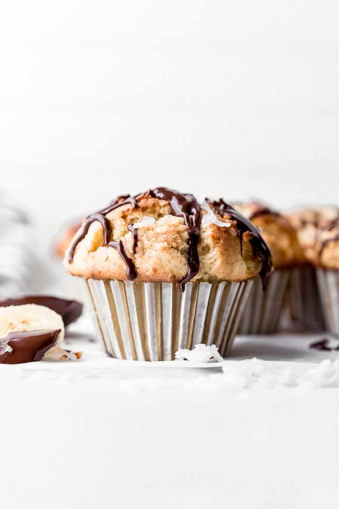 Banana coconut muffin on a white background drizzled with melted dark chocolate and grated coconut, by The Food Cafe