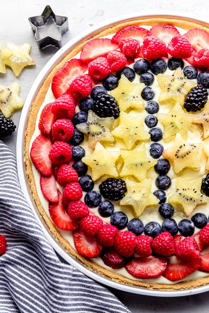 Sugar cookie fruit pizza recipe loaded with fresh berries on a white background made with a sugar cookie crust and whipped vanilla pudding, by The Food Cafe.
