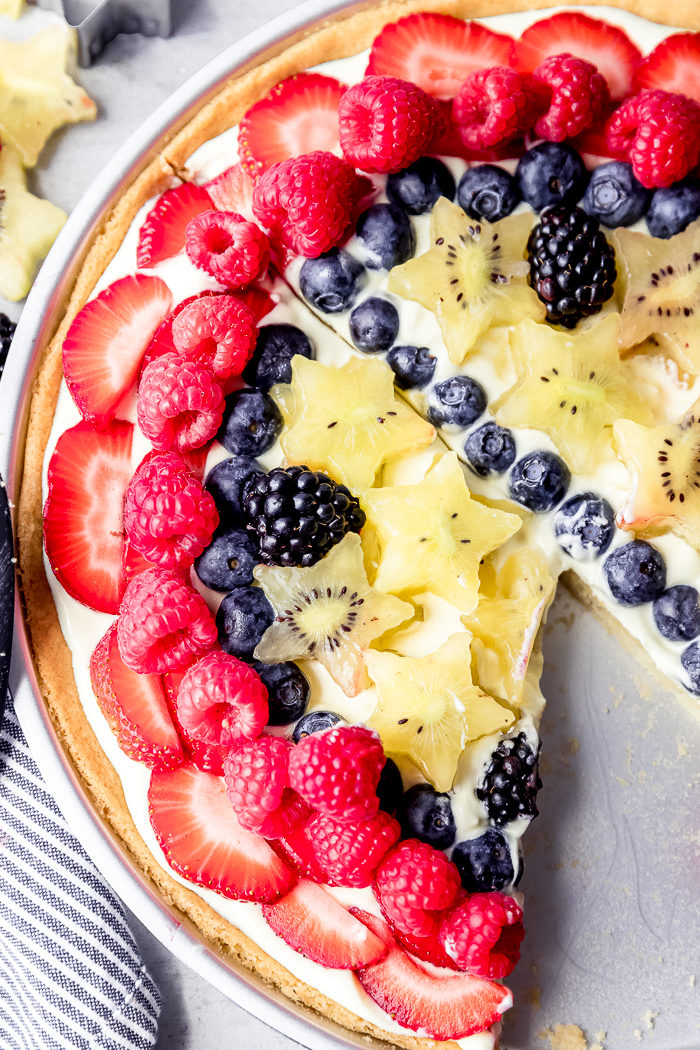 sugar cookie fruit pizza topped with vanilla whipped pudding, strawberries, blueberries, blackberries, raspberries, and kiwis with a slice missing on a white background, by The Food Cafe.