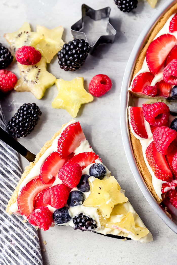 sugar cookie fruit pizza made with strawberries, blackberries, raspberries, blueberries, and kiwis's with a slice cut out on a black serving spatula on a white background, by The Food Cafe.