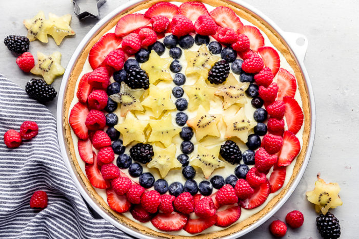 sugar cookie fruit pizza on a white background with strawberries, blackberries, raspberries, blueberries, and kiwis layered on top of whipped vanilla pudding, by the food cafe.