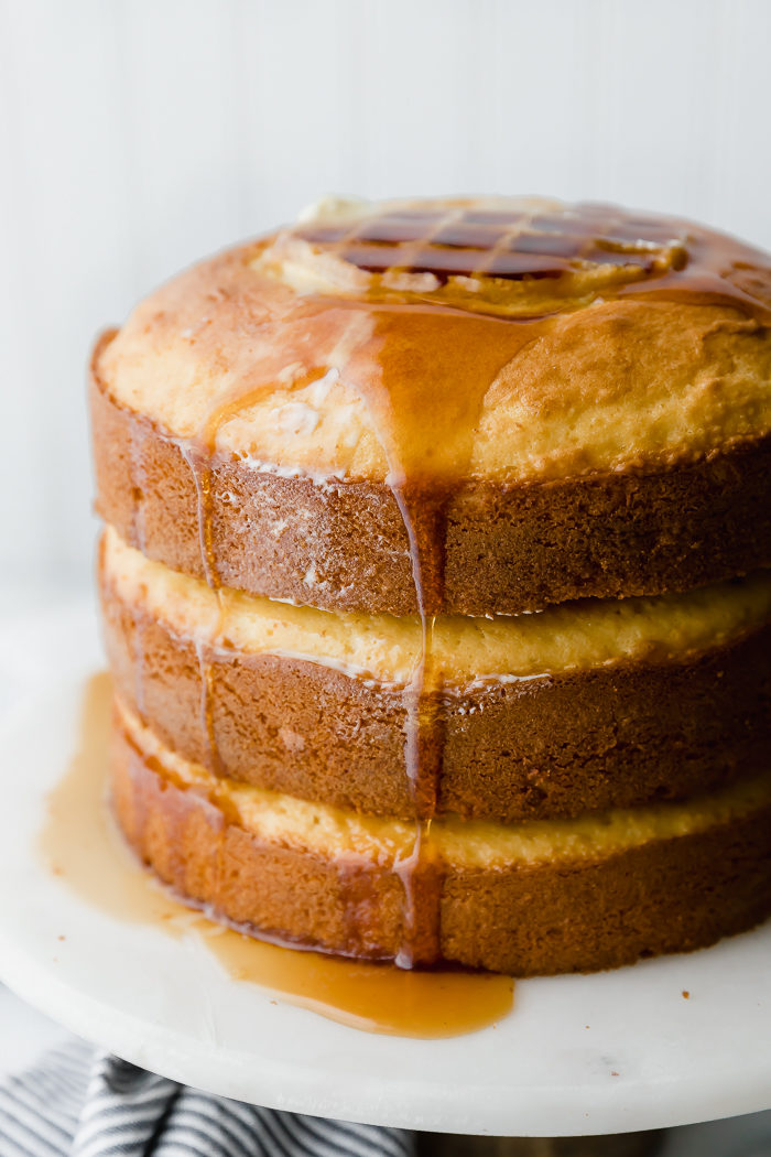 Waffle cake on a white background stacked with three yellow round cakes and waffles baked in the middle of each layer. Topped with butter and maple syrup by The Food Cafe.