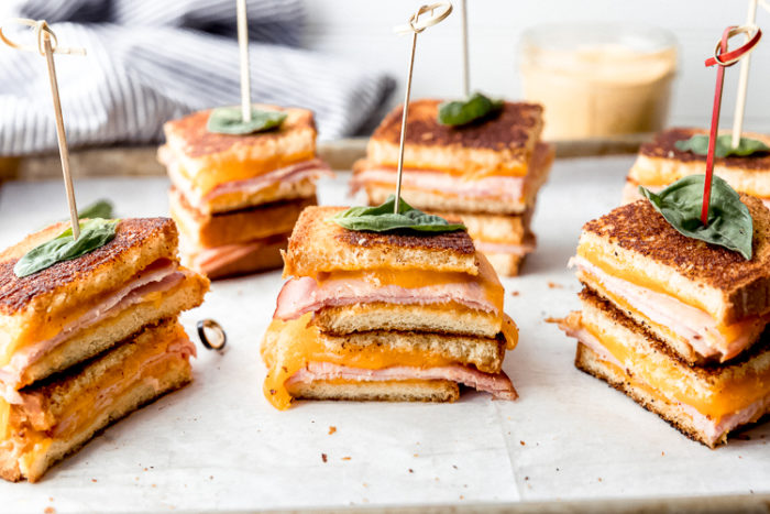 ham and cheese sandwiches, grilled, cut and stacked on top of each other and held together with a cocktail toothpick with a piece of basil on top for garnish, by The Food Cafe.