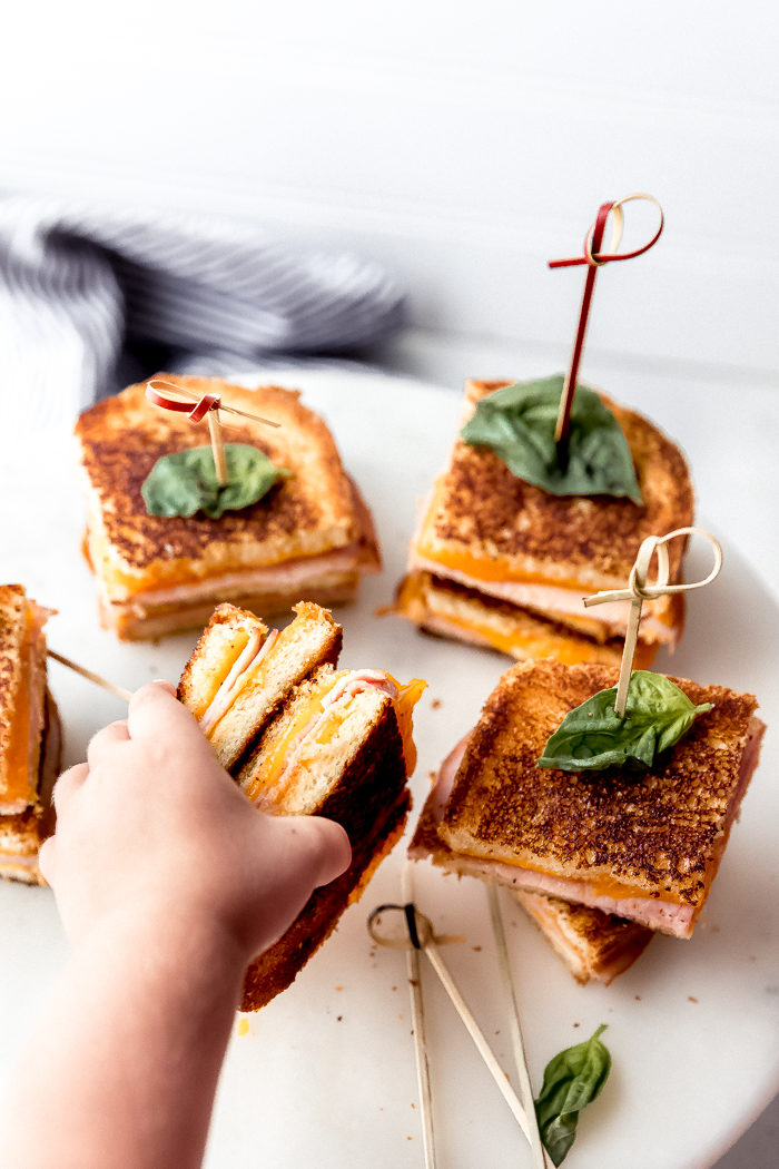 Grilled ham and cheese sandwiches on a white plate with a little girl hand reaching to grab on of the ham and cheese sandwiches, by The Food Cafe.