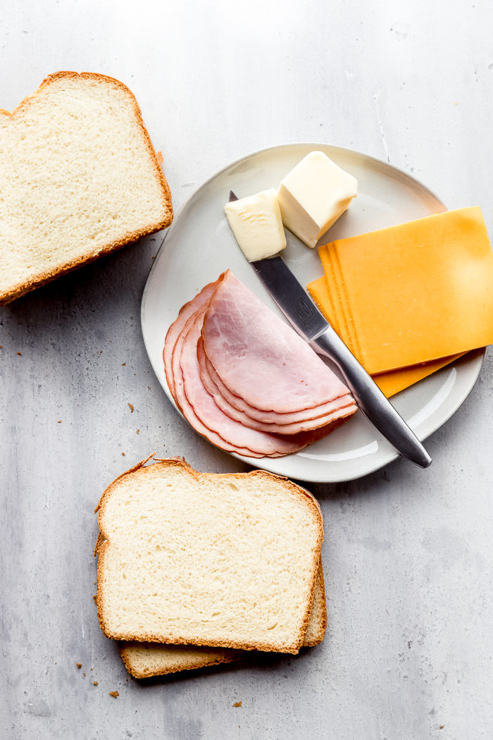 The ingredients for making grilled ham and cheese sandwiches laid out on a white background, by The Food Cafe.