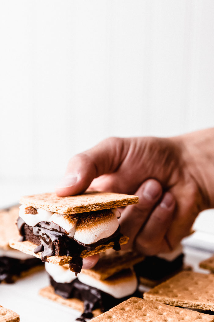 indoor s'more with graham crackers, roasted marshmallows, and a chocolate brownie being held up against a white background, by The Food Cafe.