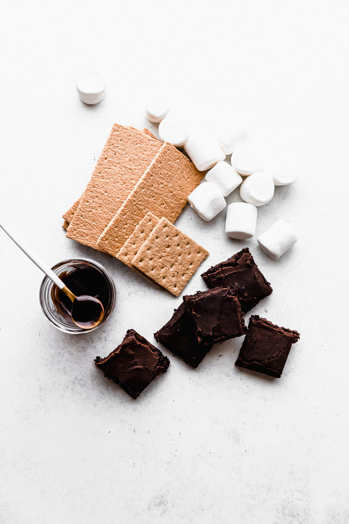A white background with the ingredients needed to make the best indoor s'mores, by The Food Cafe.