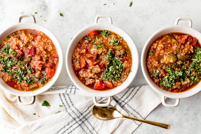 Three white bowls lined up horizontally on a white background filled with stuffed pepper soup made in the crockpot and garnished with fresh basil, by The Food Cafe.