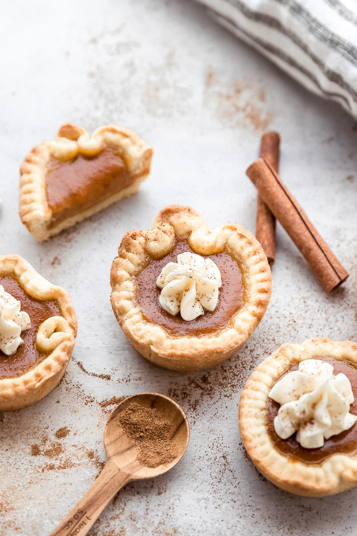 Mini pumpkin pies on a white background topped with cream cheese frosting and dusted with cinnamon by The Food Cafe.