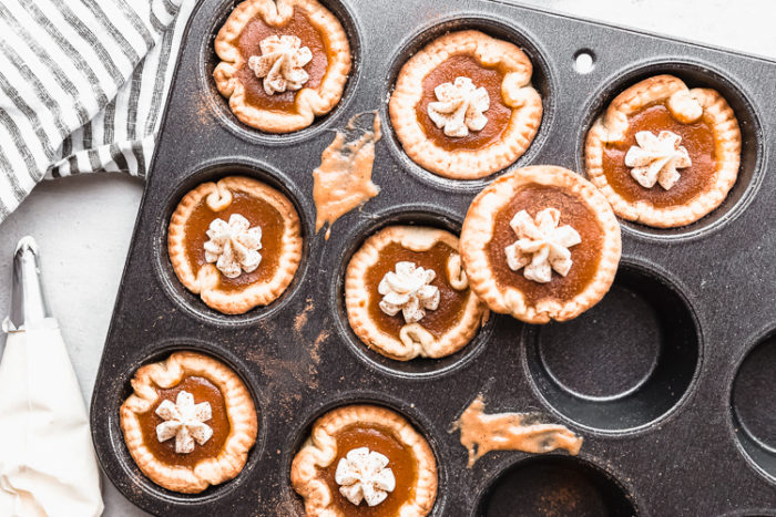 Mini pumpkin pies topped with cream cheese frosting in a muffin tin on a white background by The Food Cafe.