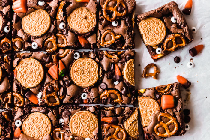 A white background with halloween brownies cut into squares decorated with oreos, pretzels, and candy corn, by The Food Cafe