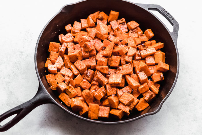 A 12 inch black cast iron skillet with seasoned sweet potatoes ready for the oven, by The Food Cafe.