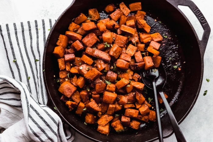 A large black skillet with cubed sweet potatoes oven roasted and sprinkled with chopped cilantro on a white background, by The Food Cafe.