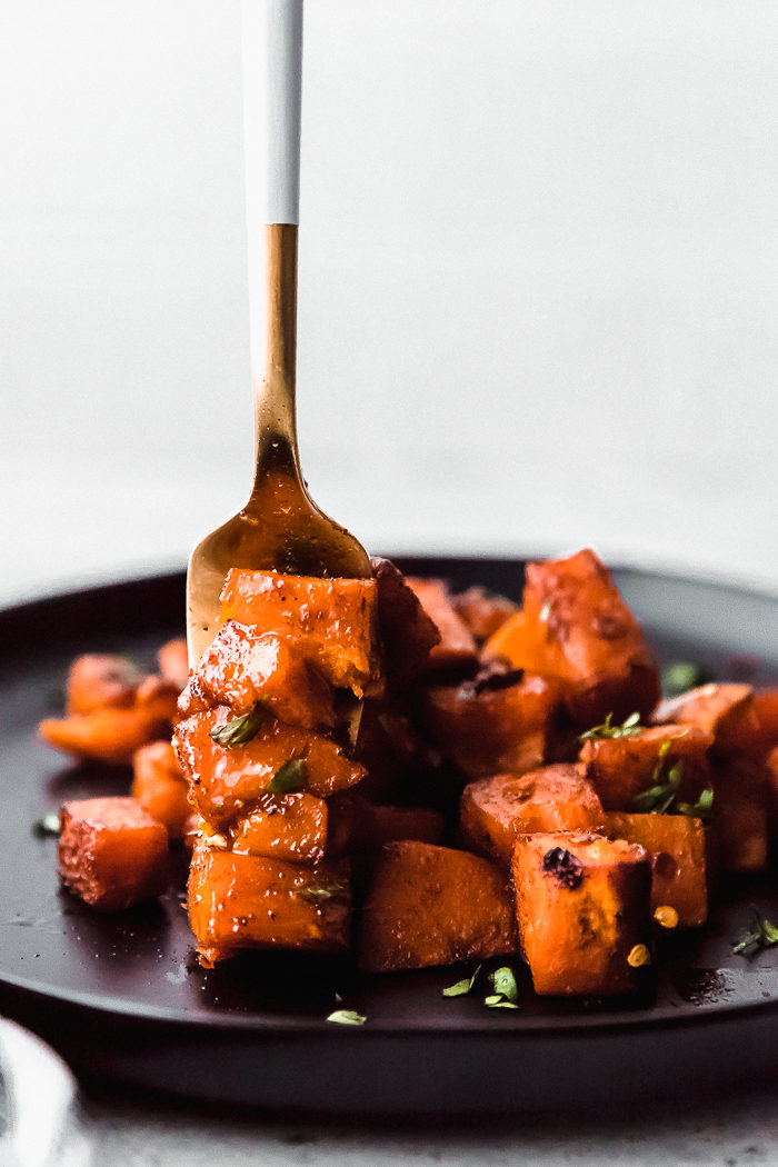 A black plate with oven roasted sweet potatoes cooked with a gold fork stabbing a few of the potatoes with its teeth by The Food Cafe.