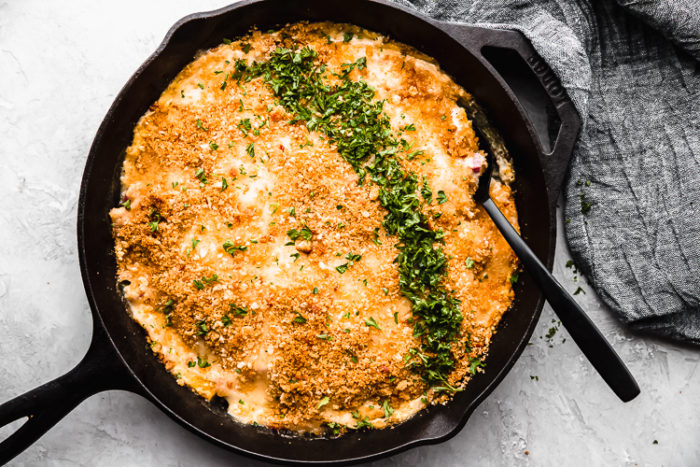 Chicken cordon bleu casserole in a black cast iron skillet with a black serving spoon on a white background that is low carb, by the food cafe.