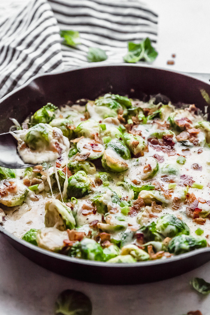 brussels sprouts topped with bacon and cheese cooked in a black cast iron skillet with a spoon pulling out the brussels sprouts with cheese stringing down, by The Food Cafe.