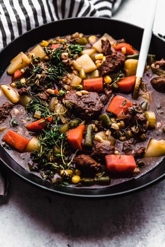 A black bowl filled with beef and barley soup on a white background with a white spoon, full of vegetables, by The Food Cafe