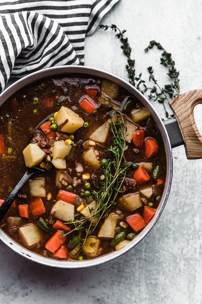 A large white soup pot sitting on a white background garnished with fresh thyme filled with beef and barley soup, the perfect hearty dinner by The Food Cafe