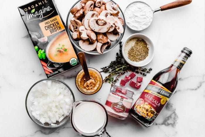 All the ingredients needed to make this cream of mushroom soup recipe on a white background, by The Food Cafe.