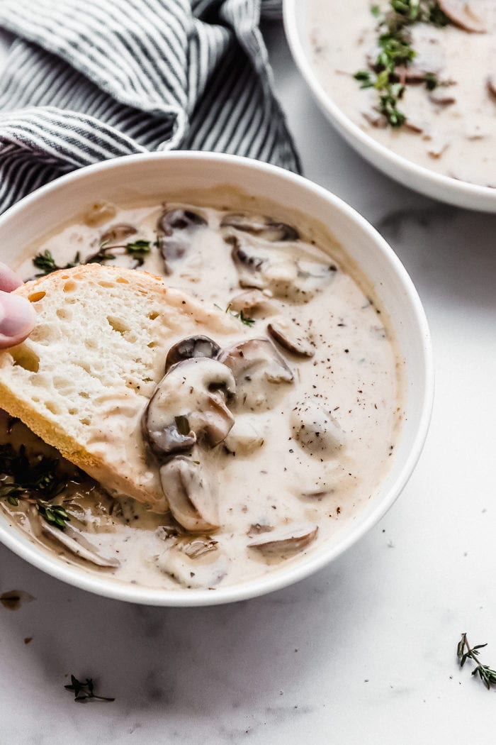 A white bowl filled with mushroom soup that is creamy with a piece of white sourdough bread taking a scoop of the soup out of the bowl, by The Food Cafe.