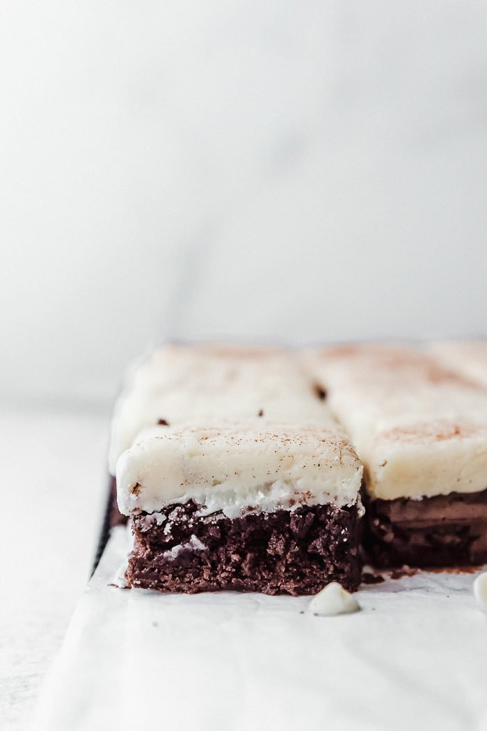 A white background with Christmas brownies on a white piece of parchment paper cut and ready to eat by The Food Cafe.