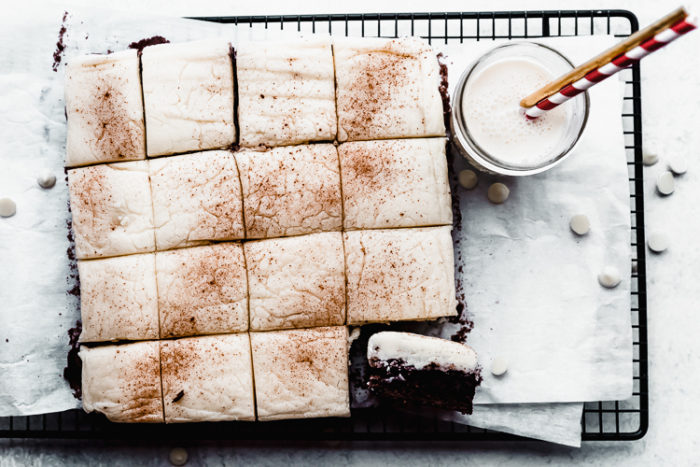 Christmas brownies cut into squares topped with eggnog frosting on a white background with a glass of milk with two straws, by The Food Cafe
