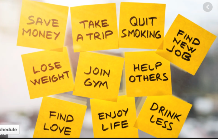 Yellow sticky notes with new year resolutions written on them.